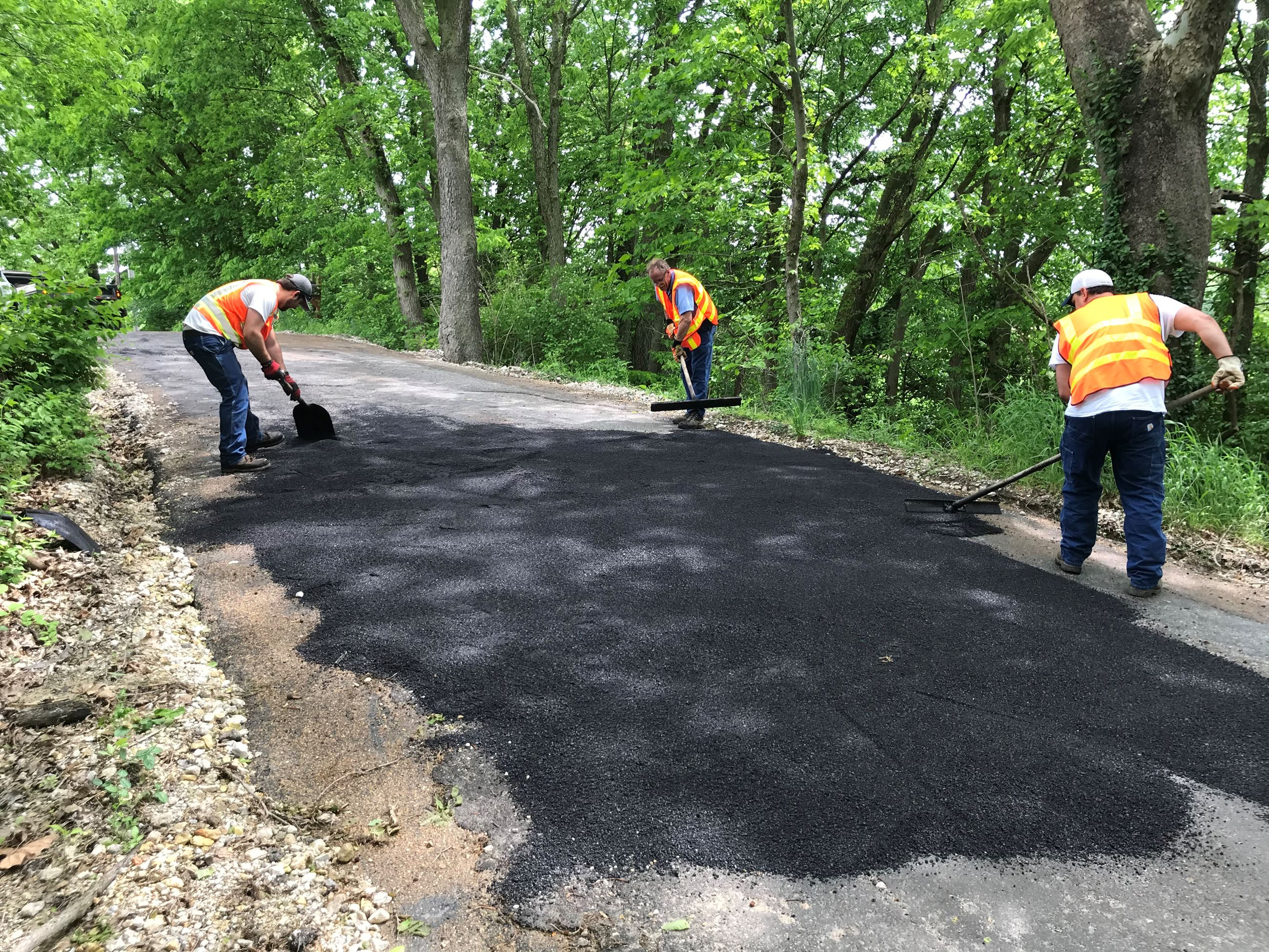 Worker putting final touches on roadway patch